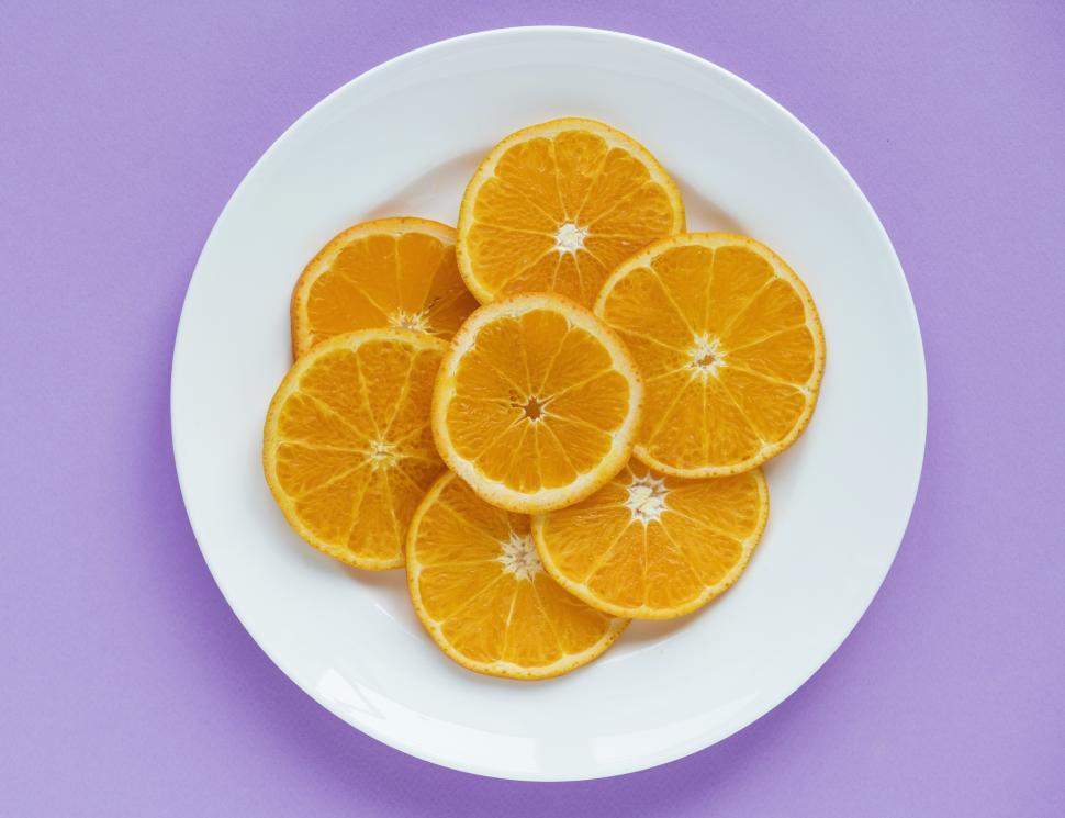 Download Free Stock HD Photo of Flat lay of orange slices arranged on white plate Online
