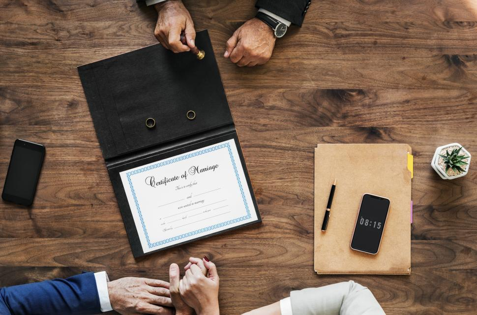 Download Free Stock HD Photo of Flat lay of of a marriage certificate with a couple s hand in hand Online