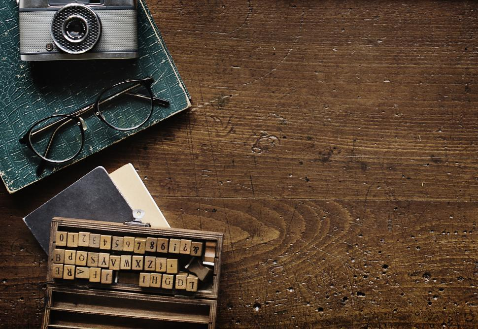 Download Free Stock Photo of Flat lay of a vintage camera and spectacles on a weathered wooden tabletop