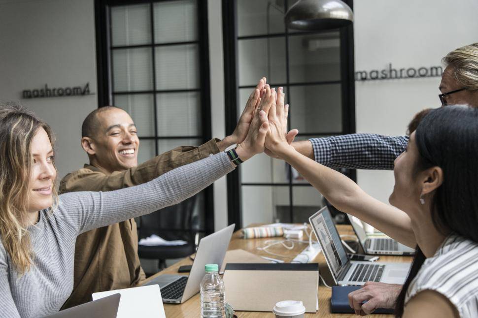 Download Free Stock HD Photo of Happy coworkers giving high five in the office Online