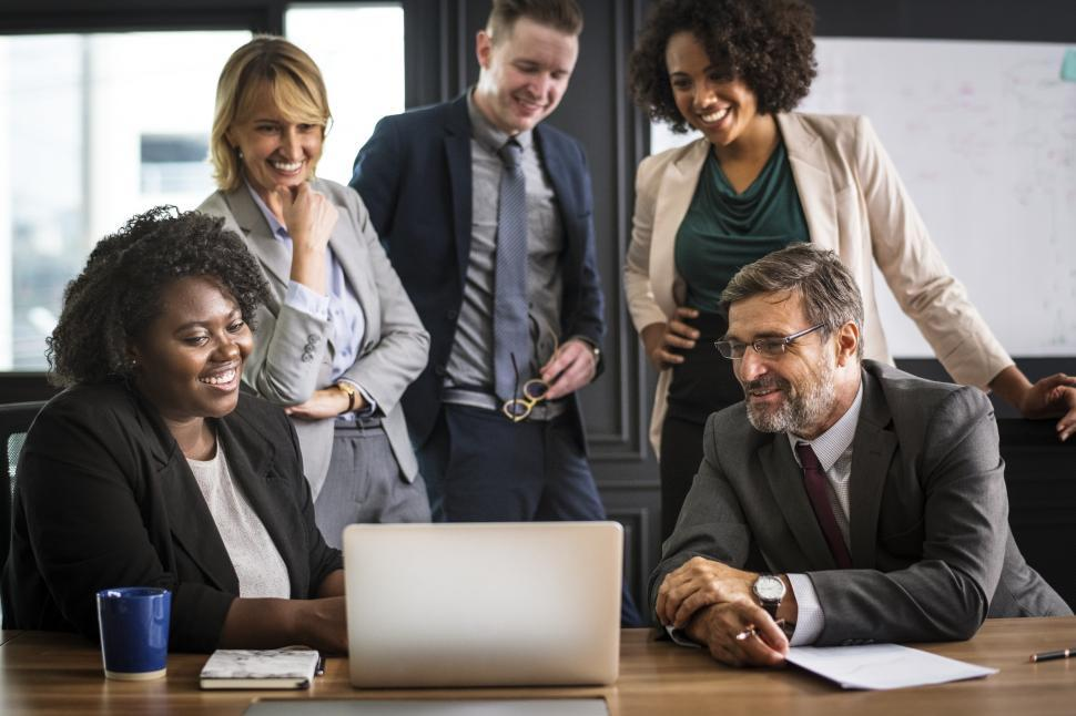 Download Free Stock HD Photo of Gathered around a laptop in a meeting Online