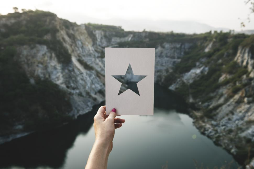 Download Free Stock Photo of A hand holding a star shaped cardboard stencil