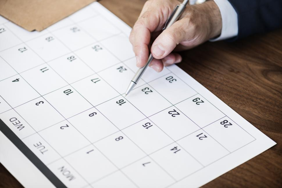 Download Free Stock Photo of Close up of a had marking date on the calendar