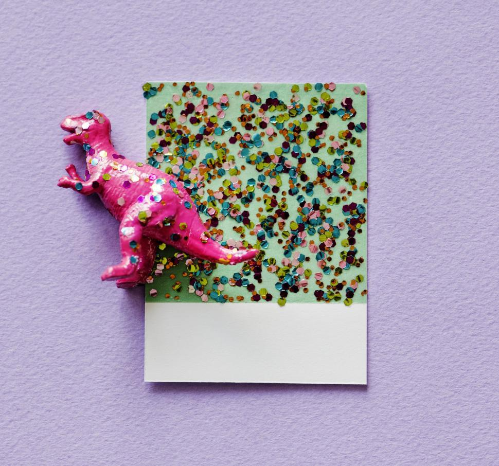 Download Free Stock HD Photo of Flay lay of a miniature glittery toy dinosaur on a spaced cardboard frame Online