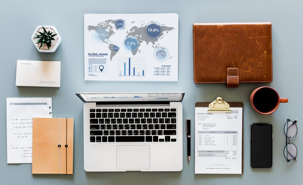 Download Free Stock Photo of World map graphic with laptop and a coffee mug along with other items