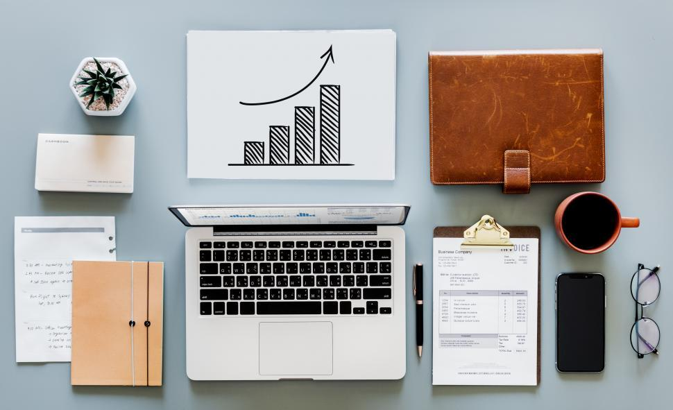 Download Free Stock HD Photo of Laptop and a coffee mug along with bar chart on the office table Online