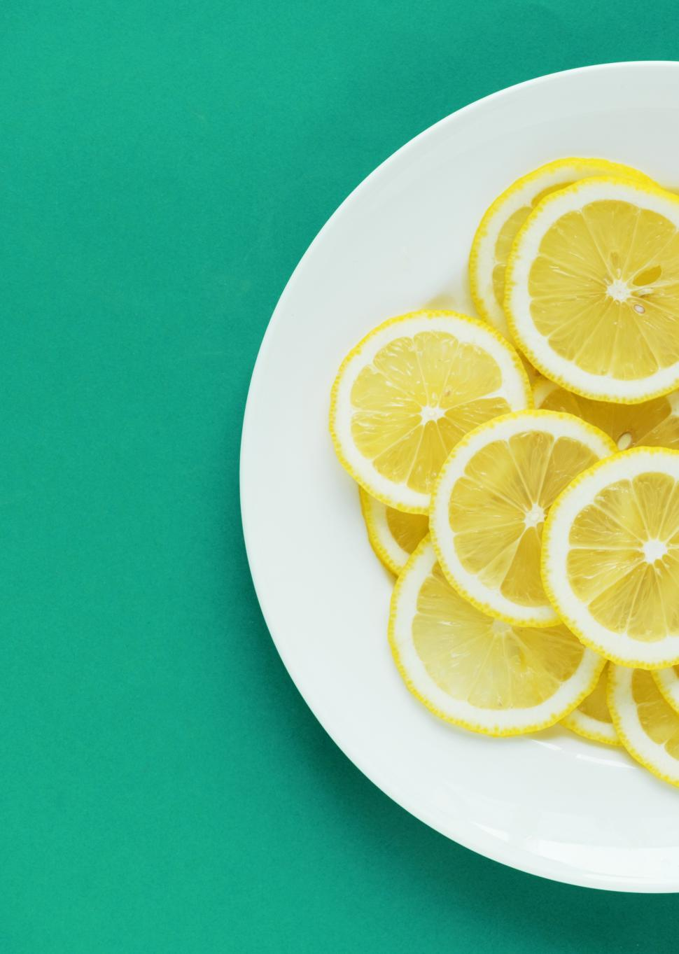 Download Free Stock HD Photo of Flat lay of lemon slices on white plate, partial view Online