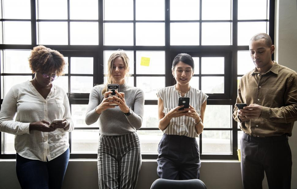 Download Free Stock HD Photo of Colleagues looking at their mobile phones Online