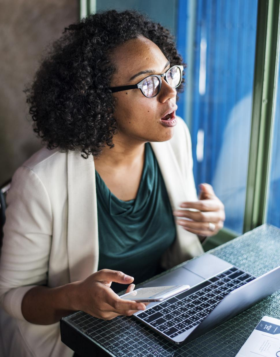 Download Free Stock Photo of A young woman talking and working on laptop