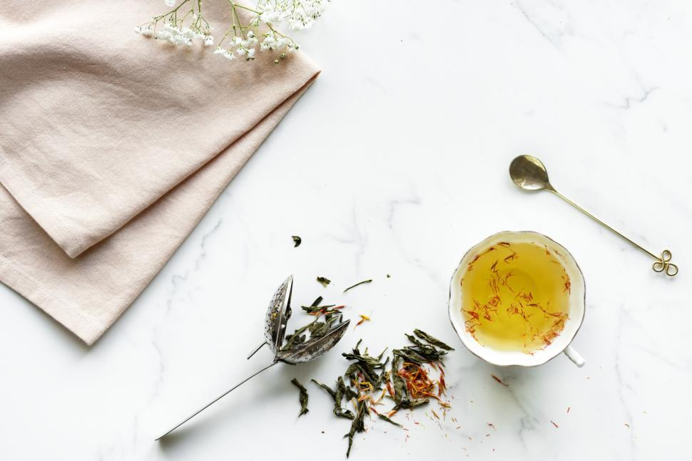 Download Free Stock Photo of Flat lay of a cup of saffron tea on marble surface