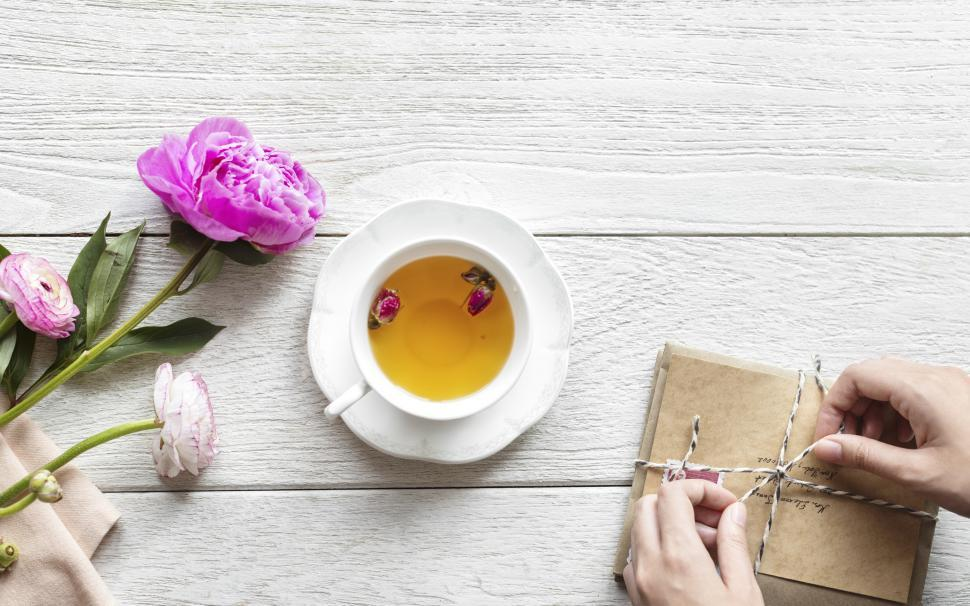 Download Free Stock HD Photo of Overhead view of a cup of herbal tea alongside a stack of envelopes being tied up Online