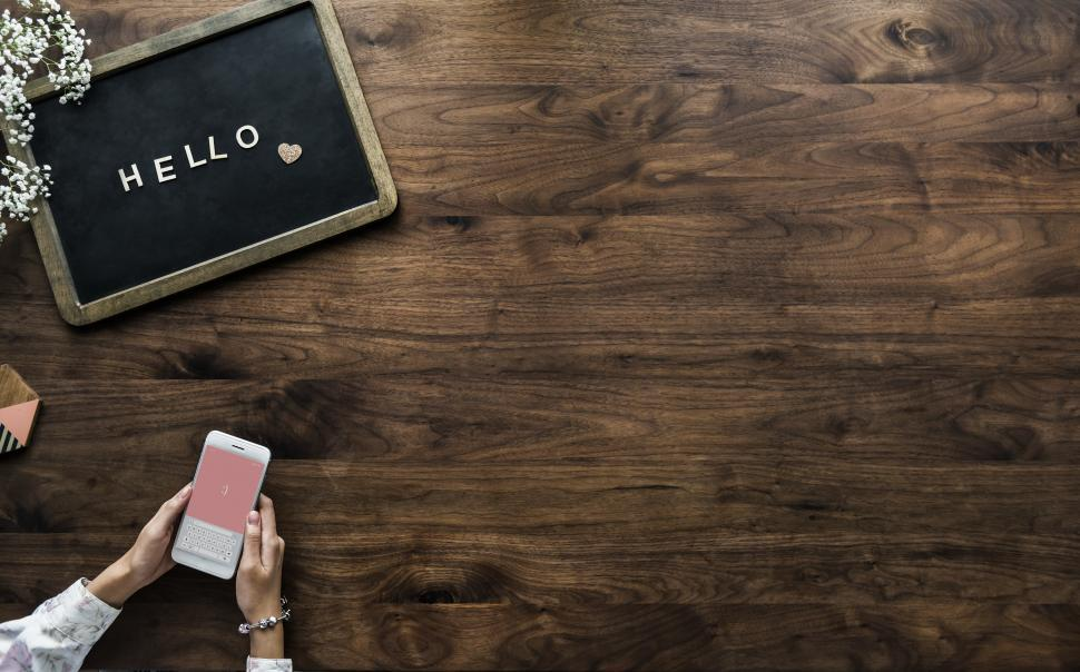 Download Free Stock Photo of Overhead view of the word HELLO on a slate board and hands holding mobile phone