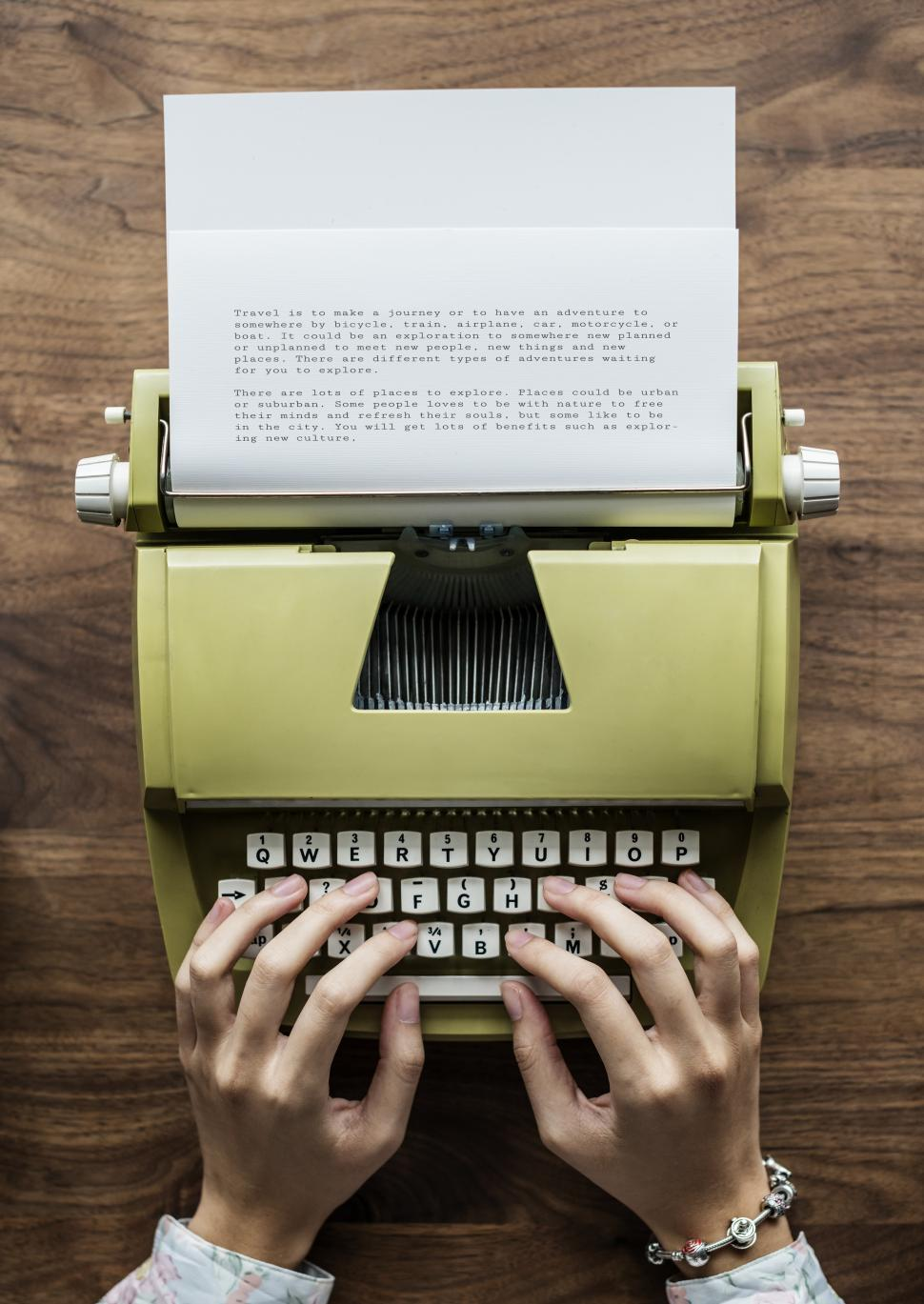 Download Free Stock HD Photo of Overhead view of hands typing a letter on a typewriter Online