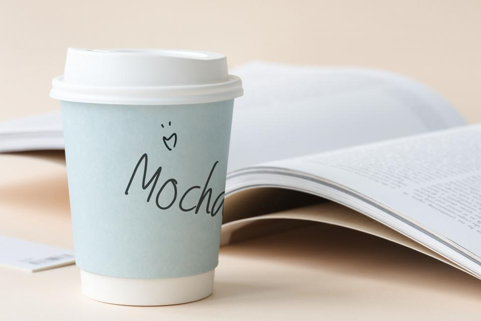 Download Free Stock Photo of Close up of a paper coffee cup with an open book in the background