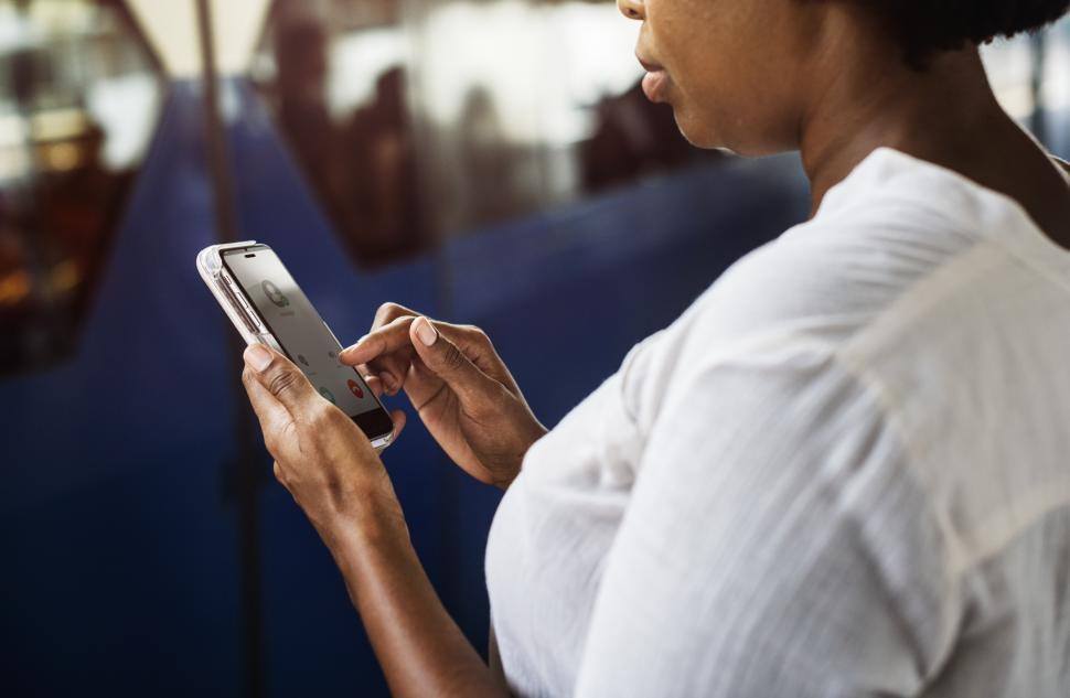 Download Free Stock Photo of A woman looks at her mobile phone, answering a call