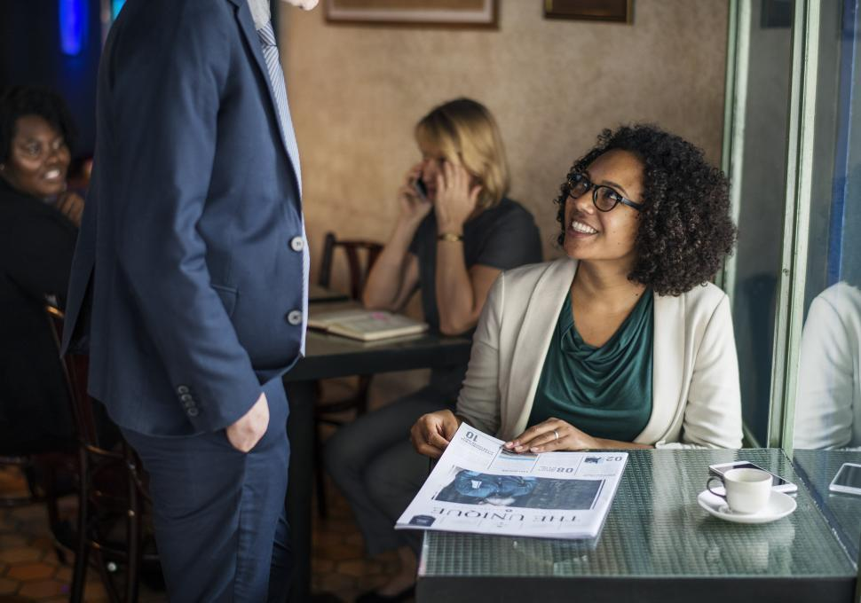 Download Free Stock Photo of A young woman greeting a colleague at a cafe