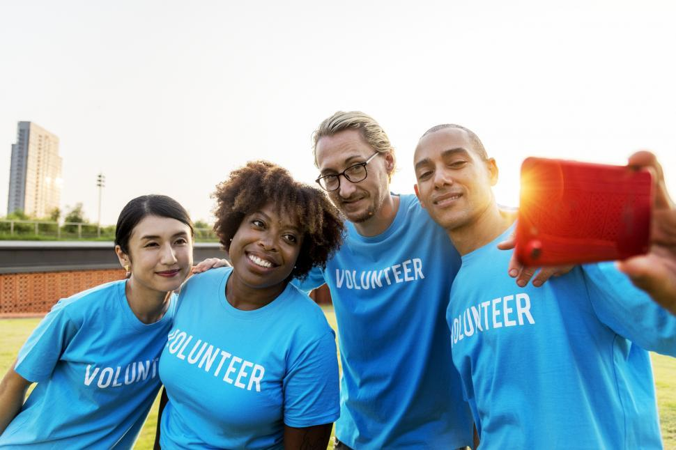 Download Free Stock Photo of A group of multiethnic volunteers taking a group photograph with mobile phone