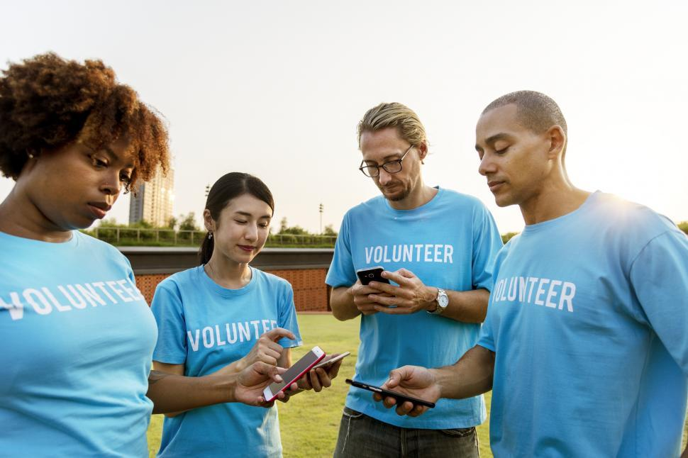 Download Free Stock Photo of A group of multiethnic volunteers looking at their mobile phones