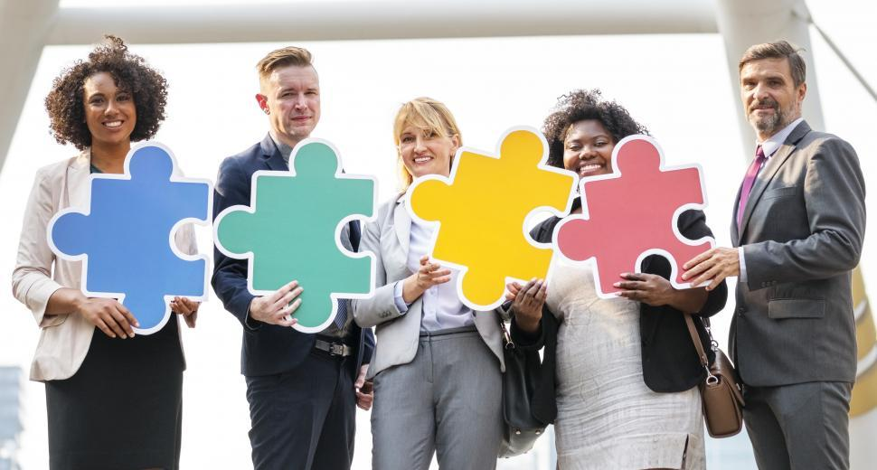Download Free Stock HD Photo of A group of colleagues holding cardboard jigsaw puzzle cutouts Online