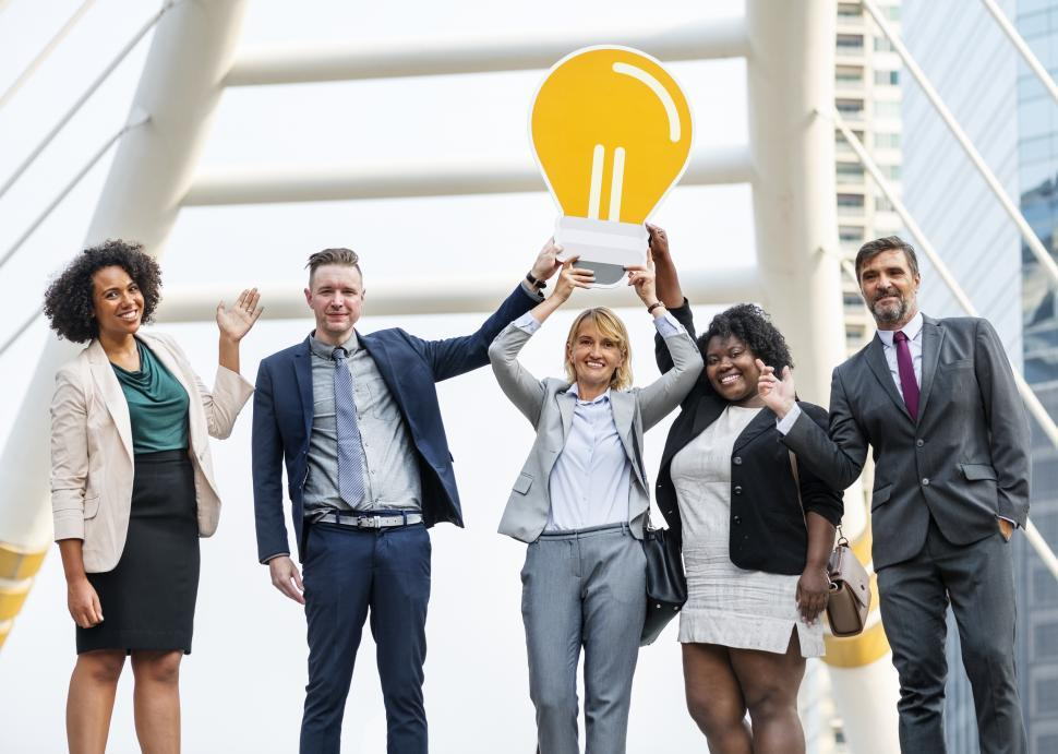 Download Free Stock HD Photo of Colleagues posing with a lightbulb symbol cardboard cutout Online