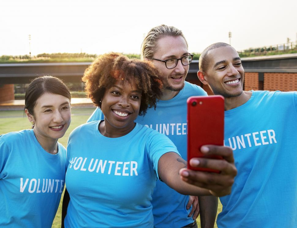Download Free Stock HD Photo of A group of volunteers taking a group selfie with red mobile phone Online