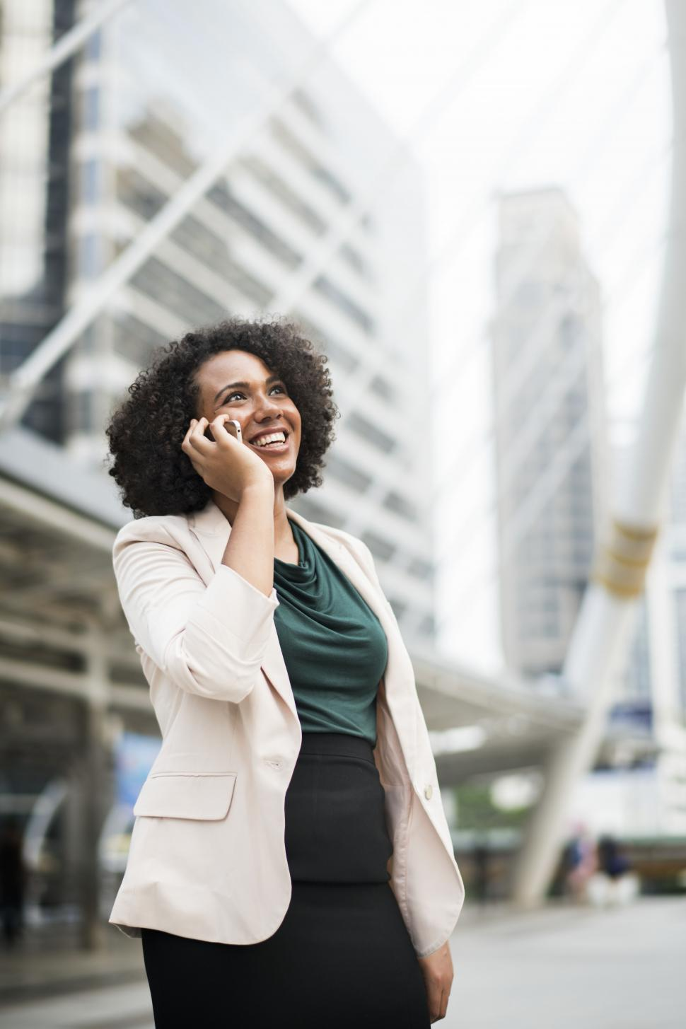 Download Free Stock Photo of A young woman outside in a city, speaking on a mobile phone