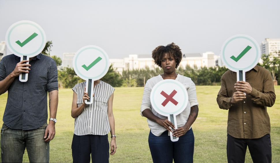 Download Free Stock HD Photo of Group of business people hiding their faces behind cardboard check mark and cross cardboard signs Online