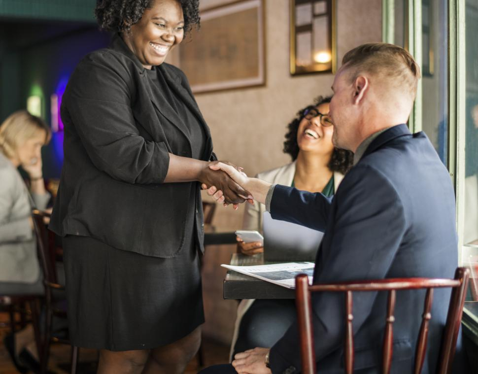Download Free Stock HD Photo of Three businesspeople at a cafe meeting and greeting Online