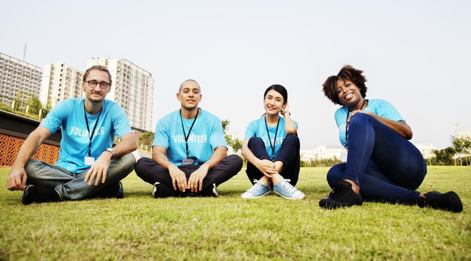 Download Free Stock HD Photo of A group of multiethnic volunteers sitting on the grass Online