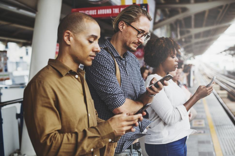 Download Free Stock HD Photo of Commuters looking at their mobile phones on a train platform Online