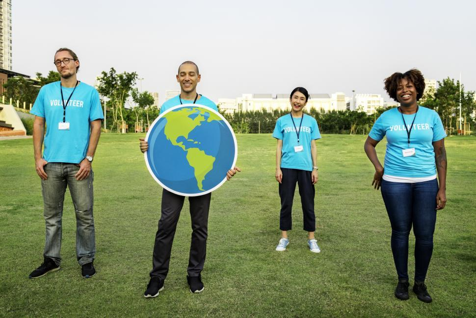Download Free Stock HD Photo of A group of multiethnic volunteers posing with a globe in a grass field Online