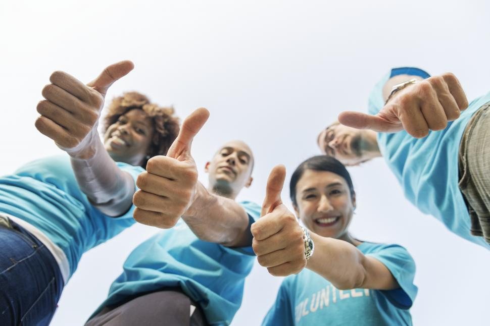 Download Free Stock HD Photo of Low angle view looking up at a volunteer group thumbs up Online