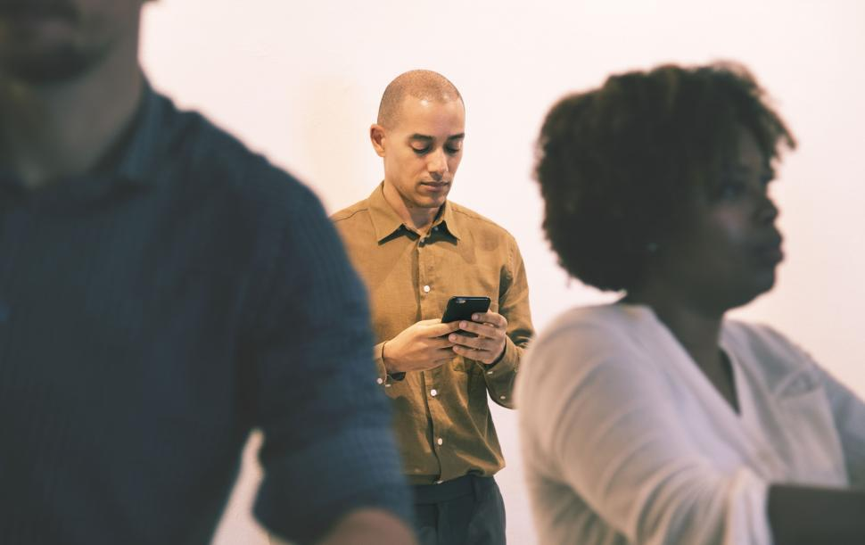 Download Free Stock HD Photo of A man behind a crowd looking at his mobile phone screen Online