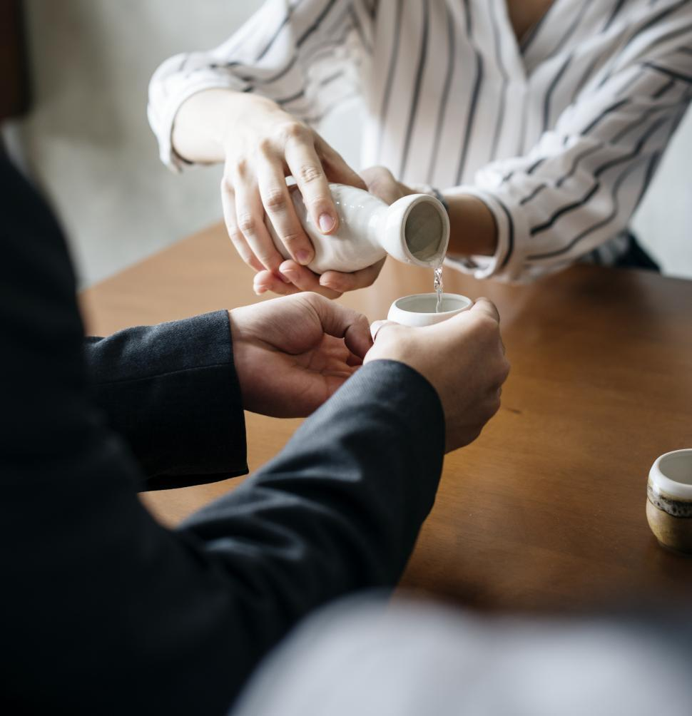 Download Free Stock Photo of Close up of hands pouring sake into Japanese traditional cup