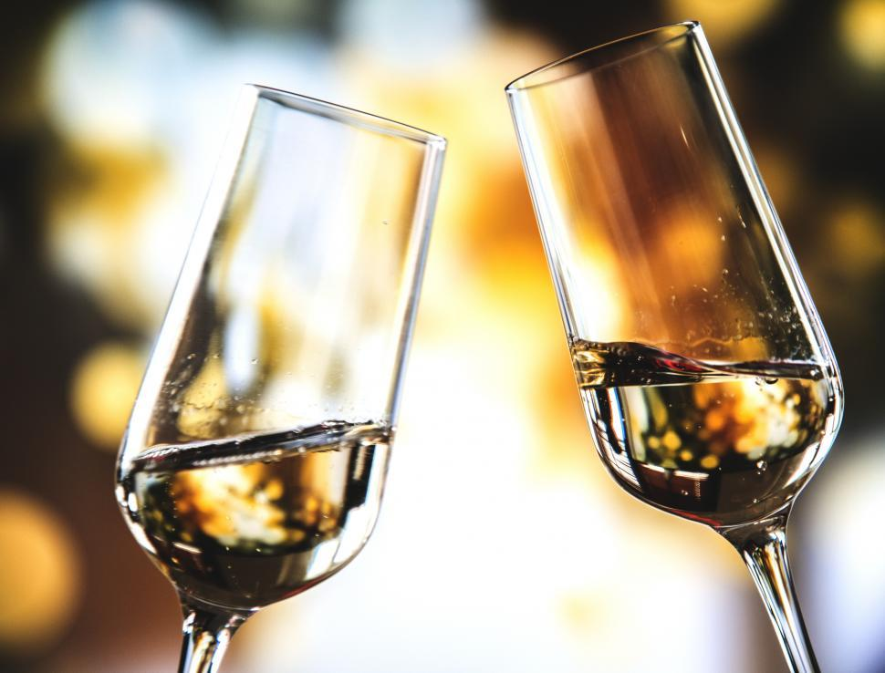 Download Free Stock Photo of Close up of two champagne glasses toasting for celebration