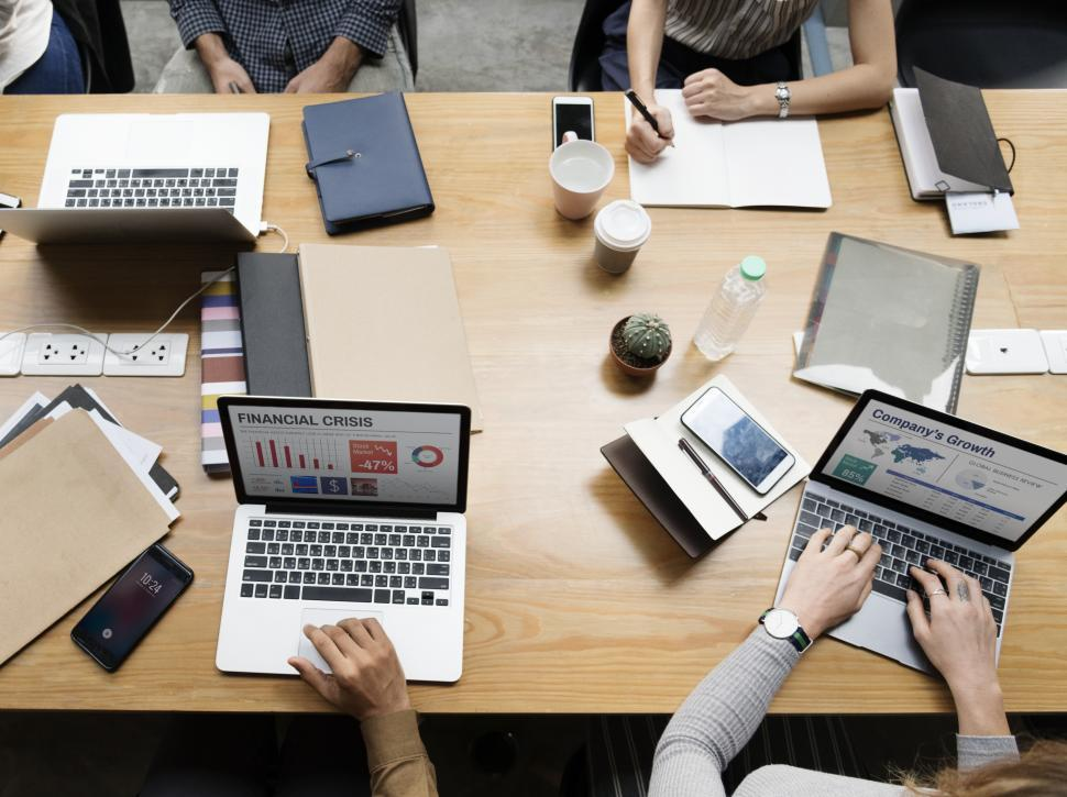 Download Free Stock Photo of Overhead view of a crowded meeting table in the office