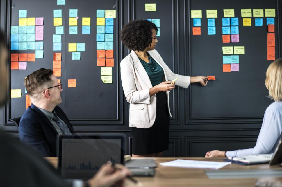 Download Free Stock Photo of A young woman in a business meeting, using sticky notes to demonstrate