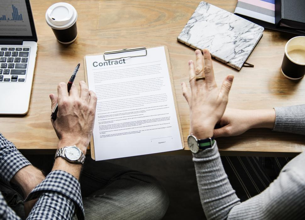 Download Free Stock Photo of Overhead view of two people s hands discussing a contract