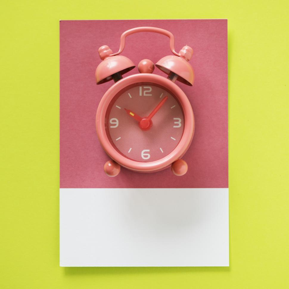 Download Free Stock Photo of Flay lay of a miniature alarm clock on matching cardboard frame