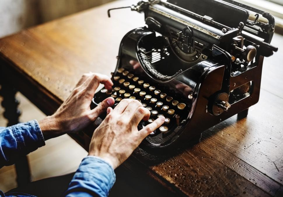 Download Free Stock Photo of Close up of hands typing on a vintage mechanical typewriter