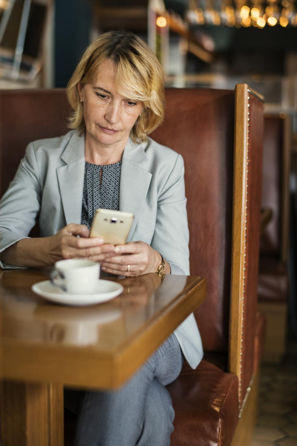 Download Free Stock HD Photo of A Caucasian businesswoman looking at her smart phone Online