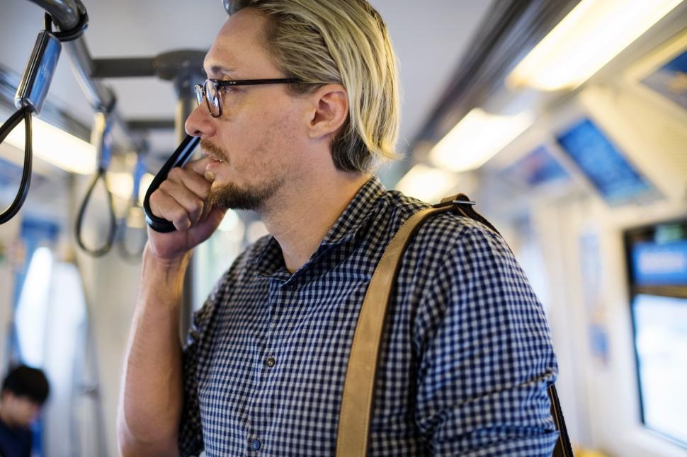Download Free Stock HD Photo of A bearded Caucasian man straphanging on the train Online