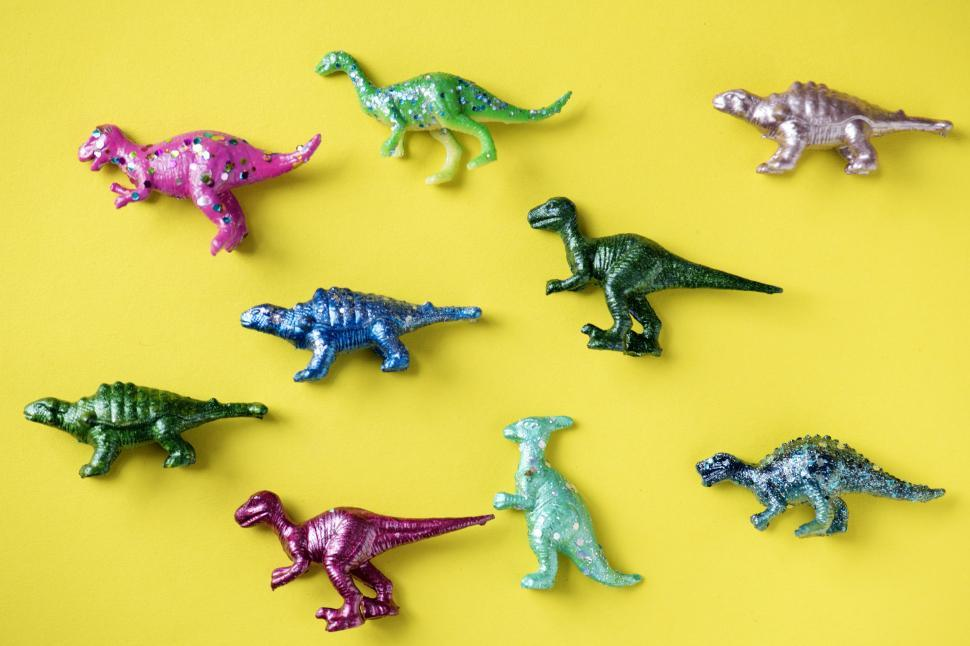 Download Free Stock HD Photo of Colorful toy dinosaurs on yellow surface Online