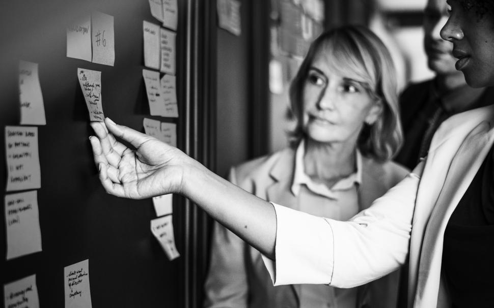 Download Free Stock HD Photo of A woman looks at sticky notes on a working board Online