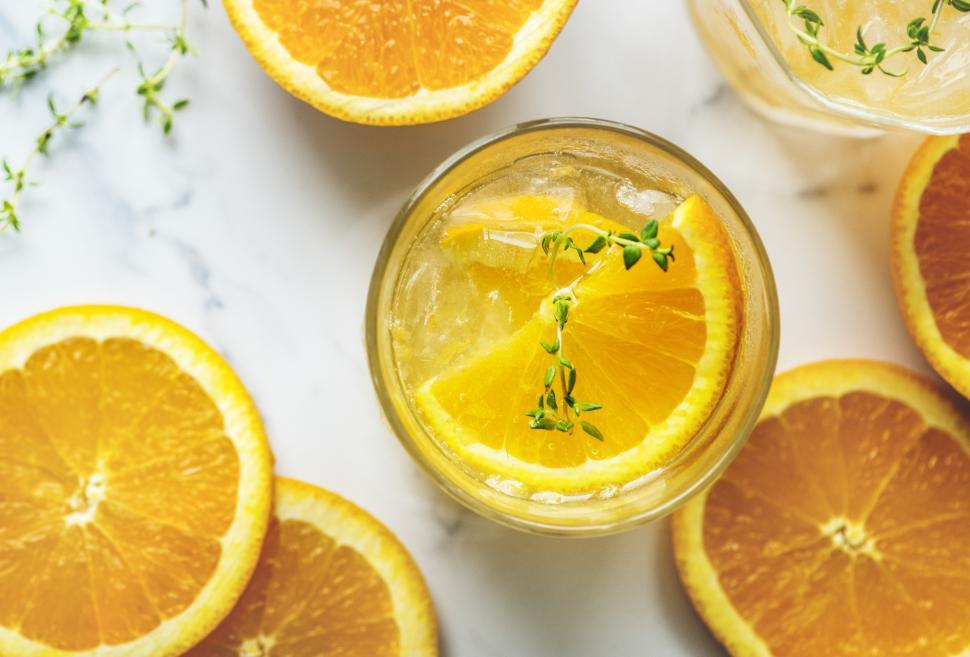 Download Free Stock HD Photo of Overhead view of chilled beverage in glasses garnished with orange slices Online