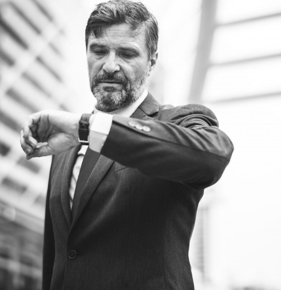 Download Free Stock Photo of A bearded businessman looks at time - black and white