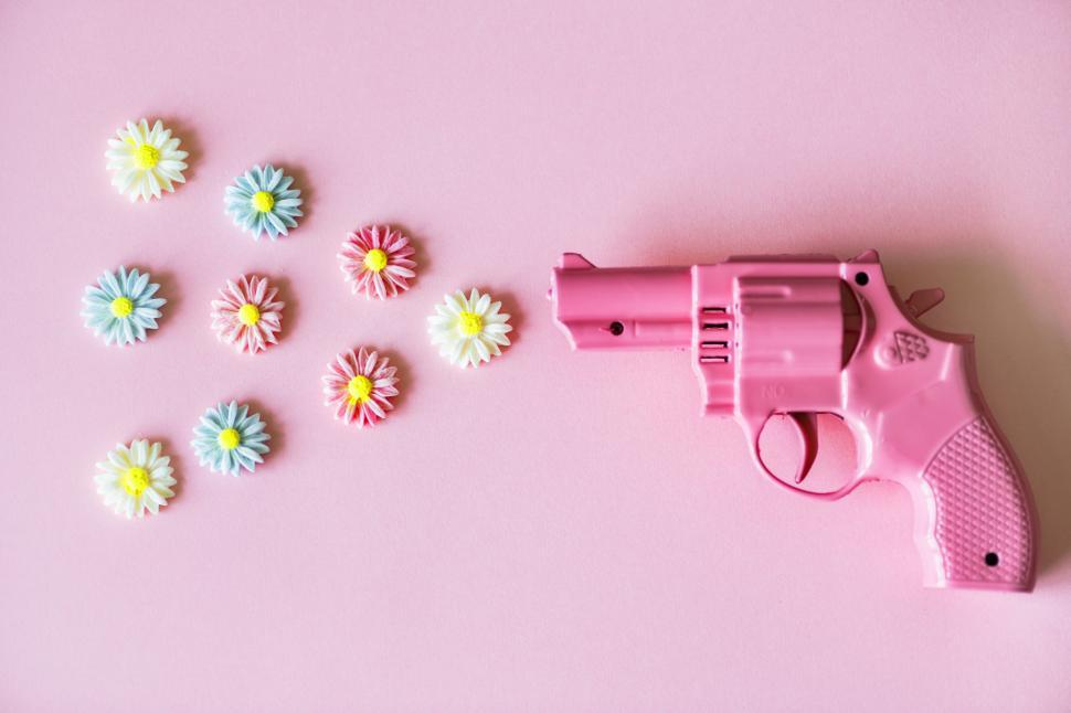 Download Free Stock HD Photo of Flat lay of clay flowers depicted as being fired from a toy gun Online