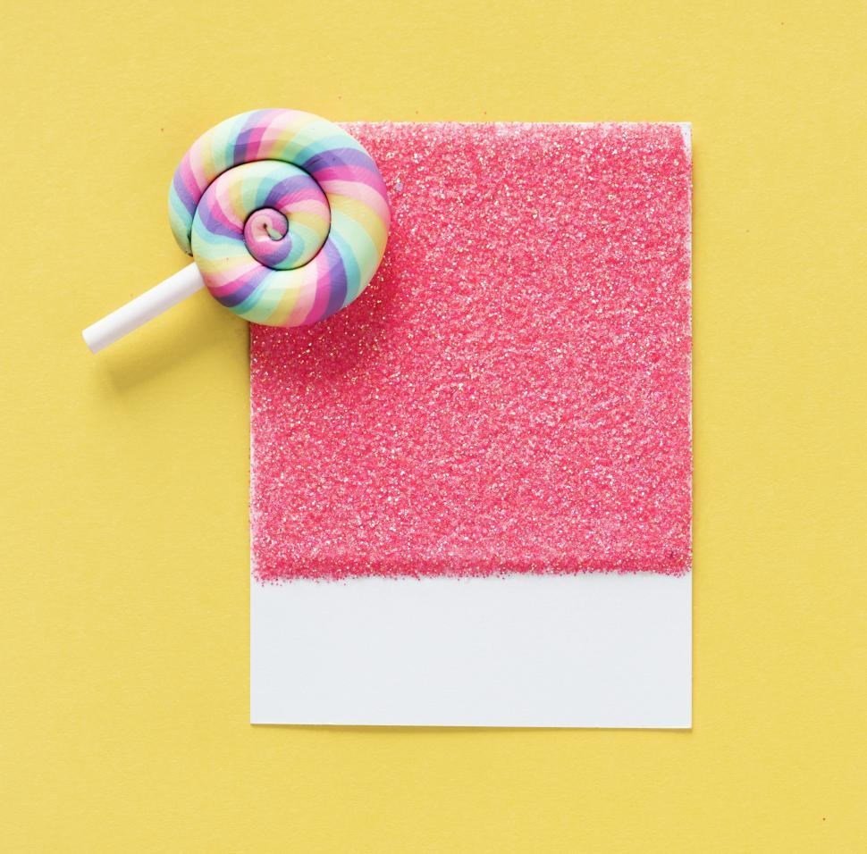 Download Free Stock Photo of Flat lay of a candy lollipop on a spaced cardboard frame
