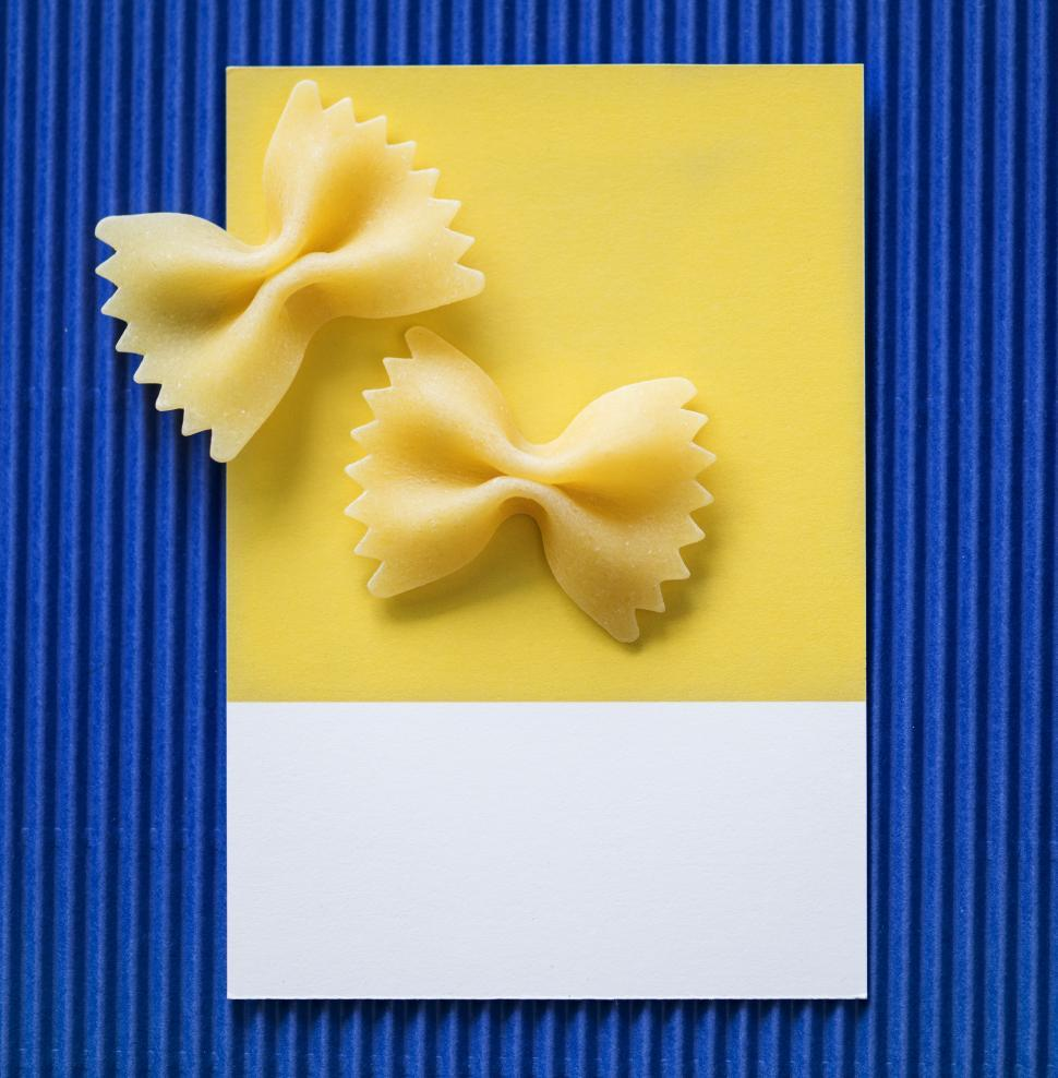 Download Free Stock HD Photo of Flat lay of Farfalle pasta Bow-tie pasta on spaced cardboard frame Online