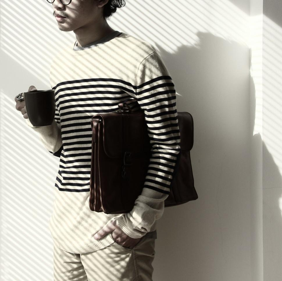 Download Free Stock Photo of Man with laptop bag and coffee mug - Light and Shadow